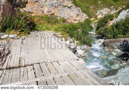 Mountain River And Wood Bridge In Vanoise National Park Alpine Valley, Savoie, French Alps