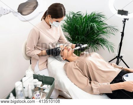 The Doctor Cosmetologist Makes The Apparatus A Procedure Of Ultrasound Cleaning Of The Facial Skin I