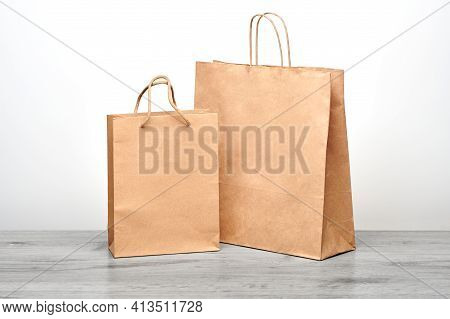 Small And Big Paper Bag With Handles Isolated. Kraft Paper Bag Mockup On Wooden Table. Recycled Shop
