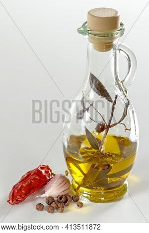 Olive Oil And Olive Sprig In A Glass Jug On A White Background. A Pod Of Hot Red Pepper, Garlic And
