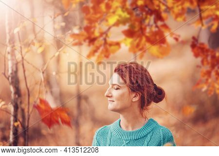 Pretty Woman With Red Hair In Autumn Forest. Adult Female Person In Green Pullover With Closed Eyes