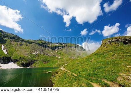 Balea Lake In Fagaras Mountain Of Romania. Beautiful Landscape In Summertime. Rocky Slopes With Gras