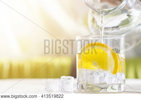 Female Hands Pouring Water From The Decanter Into A Glass Beaker With Lemon And Ice. Health And Diet
