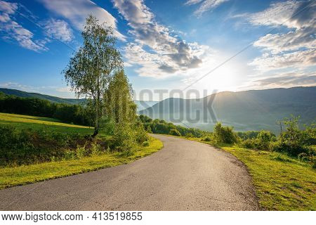 Countryside Road In Mountains On A Sunny Day. Beautiful View In To The Distant Foggy Valley From The