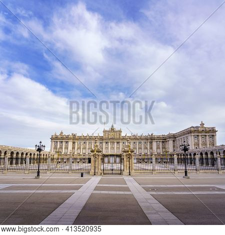 Main Facade Of The Royal Palace Of Madrid With Its Huge Esplanade And Blue Sky With Clouds At Sunris