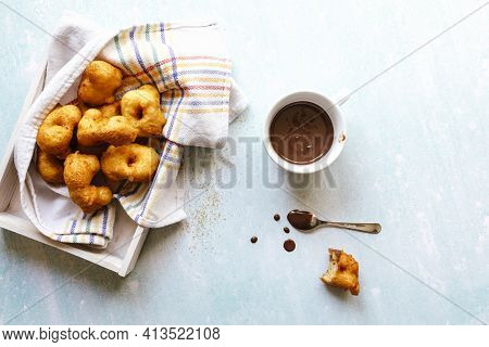 Flat Lay Of Sweet Fritter Bitten Beside A Cup With Chocolate
