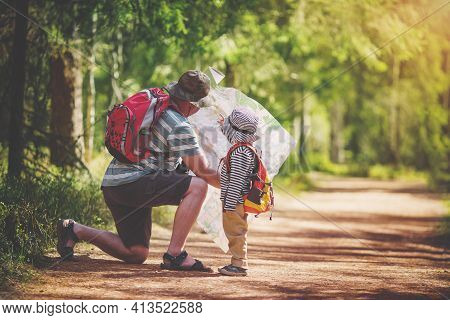 Father And Boy Going Camping With Tent In Nature. Man With Son With Backpacks Walking In The Forest