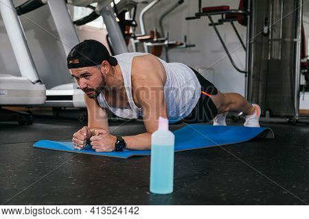 Man Doing Planks In The Gym. Hydro Alcoholic Gel, Coronavirus, Pandemic.