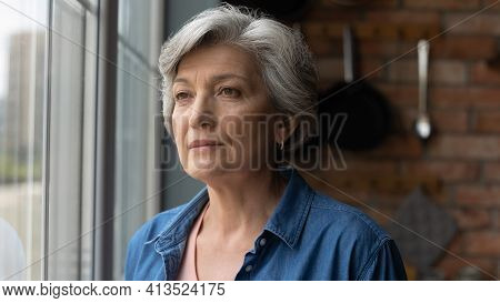 Worried Depressed Old Latin Lady Stand By Window Look Away