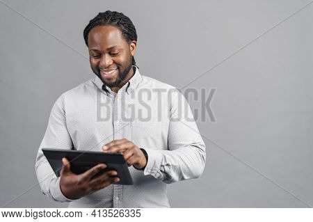 Photo Of Attractive Bearded Hispanic Man Dressed In Formal Shirt Using Tablet Computer Isolated Over