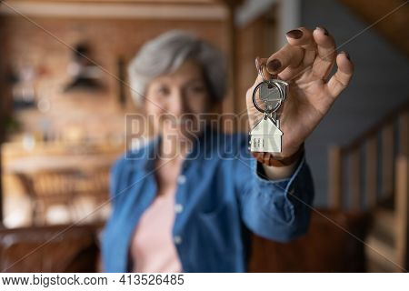 Happy Elderly Female Homeowner Pose In Country Cottage Hold Keys