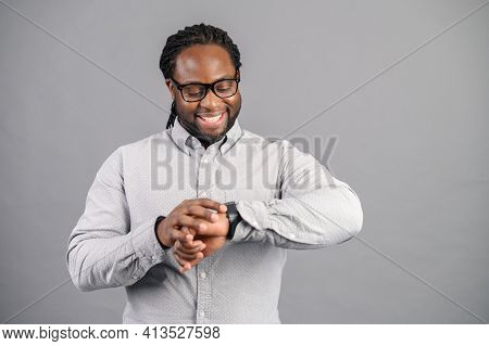 Punctual Afro American Businessman In Good Mood, Standing, Checking His Smartwatch, Received Notific
