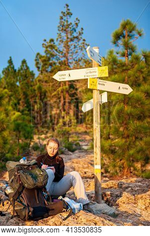 Young Woman Hiker With Backpack Sitting Under Signpost And Writing Diary. Female Trekker Backpacking