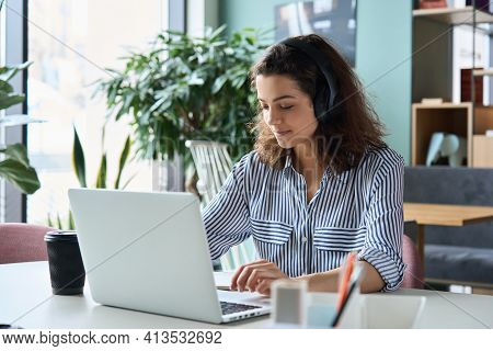 Latin Hispanic Girl College Student Wearing Headphones Taking Online Training Class On Laptop Comput