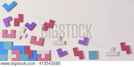 Different Colorful Shapes Wooden Puzzle Blocks On Pastel Color Background. Geometric Shapes In Diffe