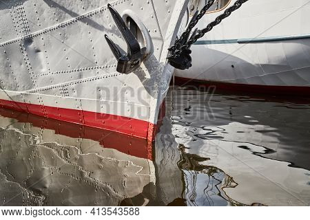 Nasal Part Of A Sailing Frigate Of White Color With An Anchor On A Nose, Bright Reflection In Water