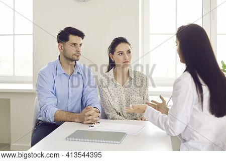 Doctor Counseling Millennial Family Couple About Medical Treatment At Clinic