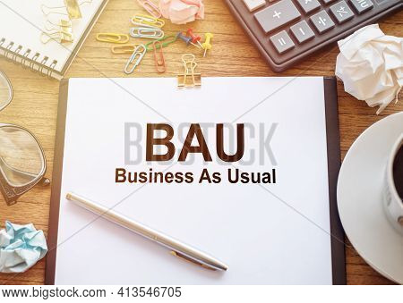 On A Wooden Table There Is An Office Sheet Of Paper With The Text Bau - Business As Usual. Business