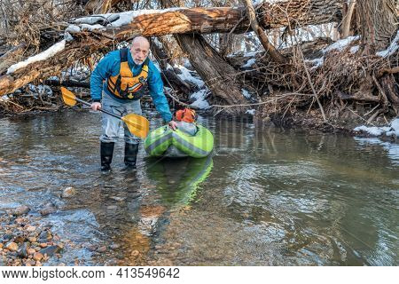 senior male paddler  with an inflatable whitewater kayak at river log jam  - Poudre River in Fort Collins, Colorado, winter or early spring scenery