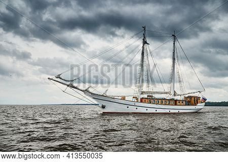 Antique Sailing Frigate Of White Color To The Sea, The Lowering Storm Sky, Sails Are Lowered, Masts