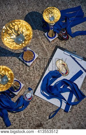 Russia.petersburg, 05 September 2020: Gold Cups And Medals Of Winners Expect The Delivery, Blue Ribb