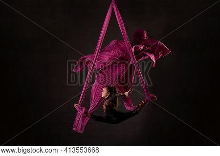 Woman Performing Acrobatic Dance On Aerial Silks