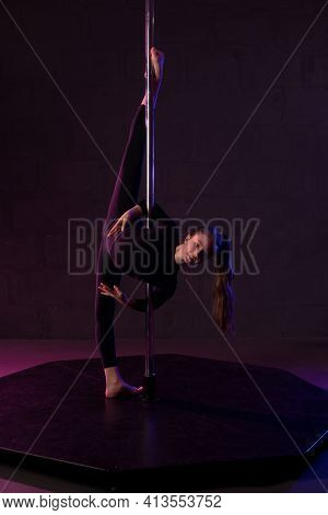 Graceful Woman Doing Gymnastic Exercise Near Pole In Darkness