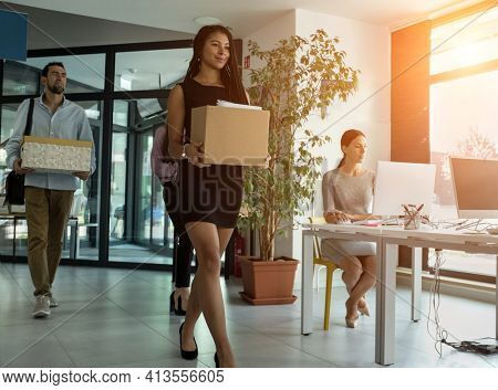 Young business people of mixed-races with boxes come back to office. Colleagues going to work in modern workspace, teamwork together.