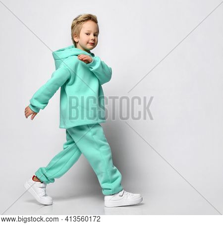 Full Portrait Of Stylish Little Boy In Warm Tracksuit Against Gray Background. A Boy In A Turquoise