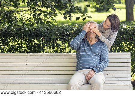 Grandfather And Grandson In The Park On A Bench Playing Hide And Seek, Activity In Nature,