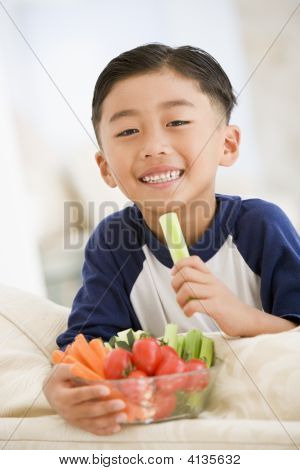 Young Boy Eating Bowl Of Vegetables In Living Room Smiling