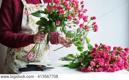 Close-up Of A Woman Florist's Hand In A Flower Apron Making A Bouquet Of Pink Roses In A Flower Shop