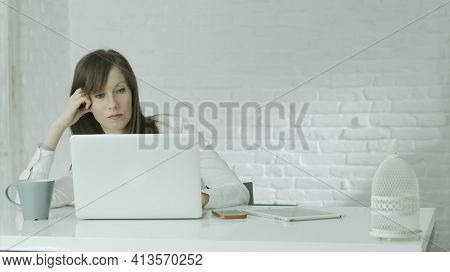 Woman working at desk with laptop in white room. Looking bored and troubled. White background and copy space.