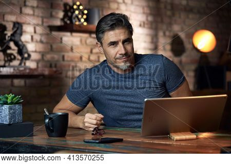 50s man working online with laptop computer at home sitting at desk, smiling. Home office, browsing internet, study room, Businessman working from home.