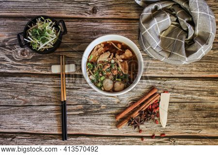 Egg Noodle With Pork And Vegetable In Five Spices Black Soup On Wooden Table Top View