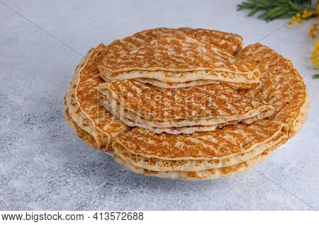 Folded Baked French Crepes Or Russians Blinis In A Round Plate On A Light Background.