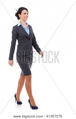 young business woman is walking. She is smiling and looking away from the camera isolated over white background