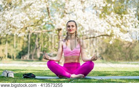 Woman doing yoga in spring park
