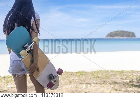 Young Women Hold Surf Skate Board With Beach Background. Women Stand With Surf Skate Relax And Enjoy