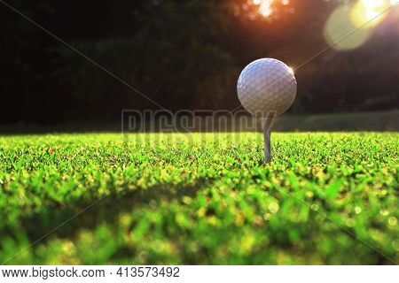 The White Golf Ball On The Tee Stand Closely Of Golf Players On The Green Lawn, There Is Sunshine.