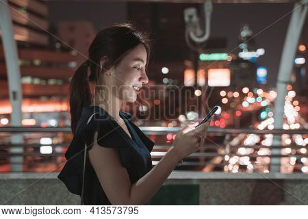 Side-view Of Beautiful Young Asian Happy Woman Standing Over Footbridge Checking Smartphone And Brow