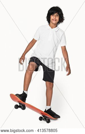 Teenage skater in white polo t-shirt sporty youth fashion studio shoot