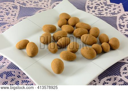 Cocoa Dusted Almonds Snack On White Dessert Plate On Lace Table Runner
