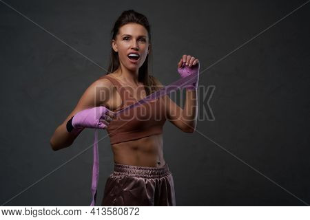 Middleaged Female Boxer Poses In Dark Background With Bandaged Hands