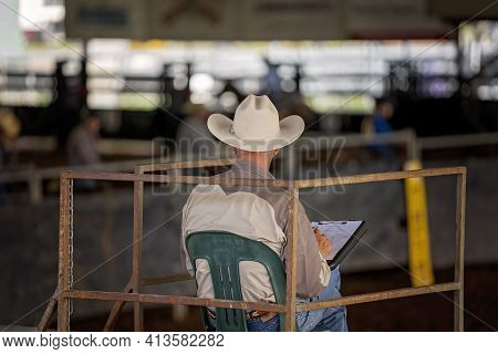 Judge In Cowboy Attire Sits In Tower Judging A Cutting Competition