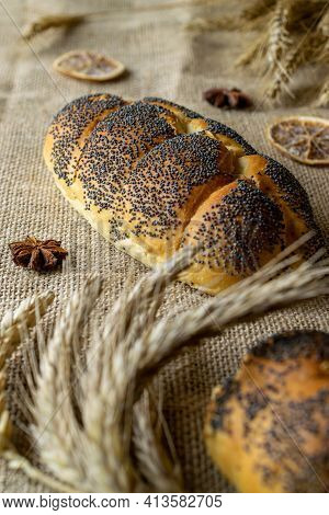 Whole Wheat Bread. Fresh Loaf Of Rustic Traditional Bread With Poppy Seeds, Wheat Grain Ear On Linen