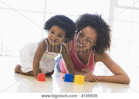 Mother And Daughter Indoors Playing And Smiling