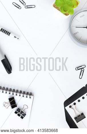 Top View On A White Desktop Background. Paper Clips, Notepad And Pen. Desktop Mockup Scene With Copy
