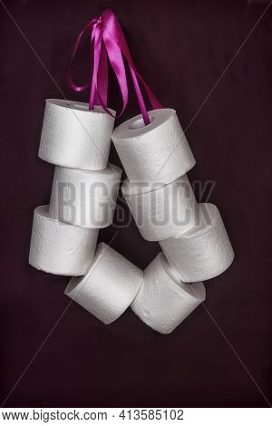 On A Dark Background, A Roll Of White Toilet Paper Is Connected By A Ribbon In A Bundle. Front View,