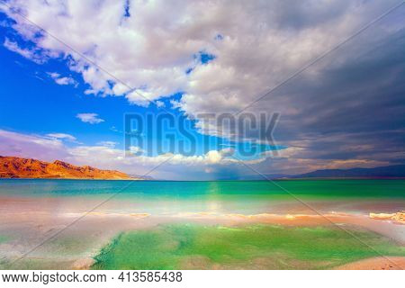 Israel, legendary Dead Sea. Low winter clouds are reflected in the green water. The smooth surface of the salty sea reflects the sky and clouds.